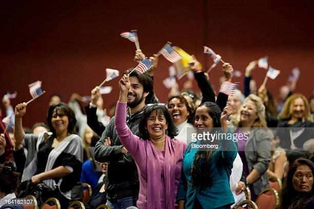 People from Mexico cheer and wave US flags during a naturalization ceremony in San Diego California US on Wednesday March 20 2013 More than 700...