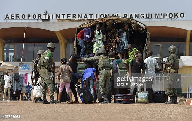 People from the Cameroonian community get off a truck as they arrive at the Bangui International airport escorted by Cameroonian soldiers part of the...