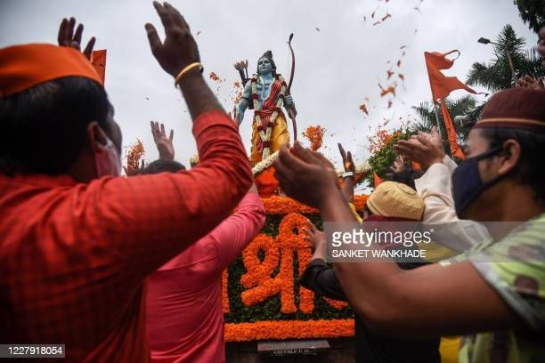 People from the Hindu and Muslim communities celebrate around a 7feet tall statue of Lord Ram the foundation stone of a Lord Ram temple in Ayodhya in...