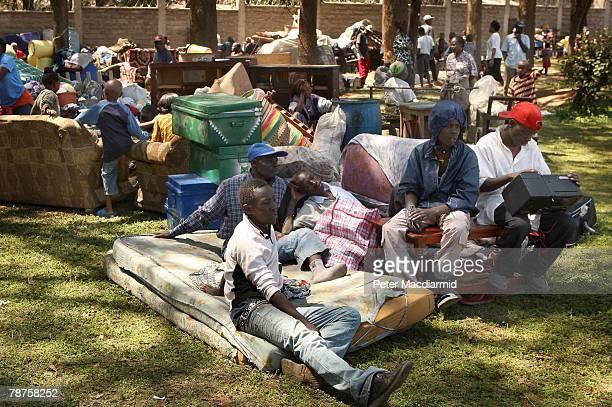 People from the Kikuyu tribe sit with their belongings outside The Kenyan Air Force base on January 4 2008 in Nairobi Kenya Kikuyu people fled from...