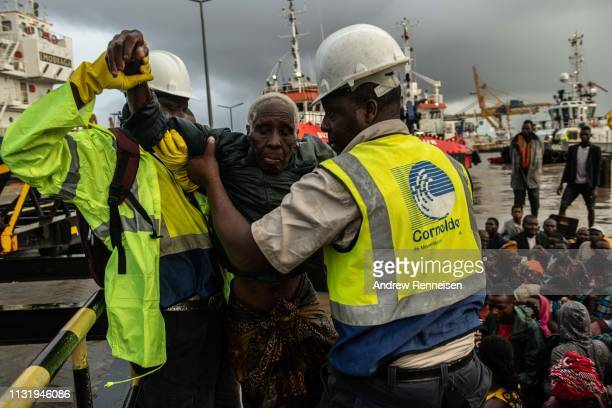 People from the town of Buzi are helped off a boat at Beira Port after being rescued on March 22 2019 in Beira Mozambique Thousands of people are...
