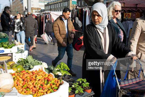 People from various ethnic backgrounds particularly from the Muslim community around the market on Whitechapel High Street in East London United...