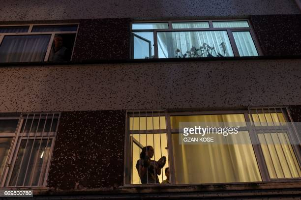 """People from windows cheer as supporters of """"No"""" gather, at the Besiktas district, in Istanbul, on April 17, 2017 to protest following the results in..."""