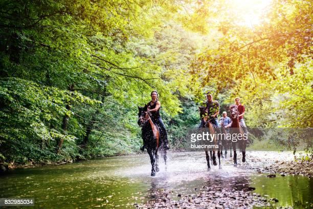 la gente galoppa il cavallo attraverso il torrente - andare a cavallo foto e immagini stock