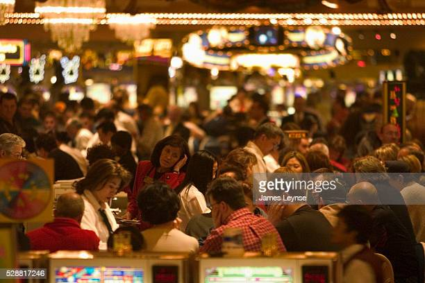 People gambling at slot machines and gaming tables at a casino in Las Vegas