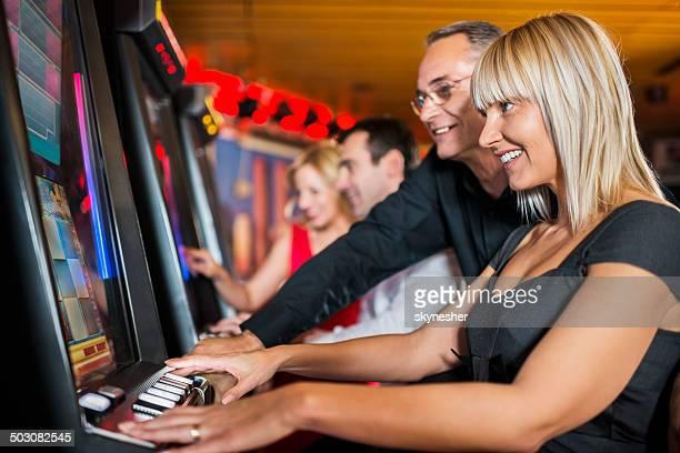 People gambling on slot machines.