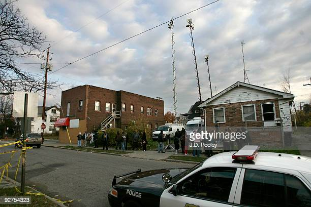 People gather across the street from the home of Anthony Sowell November 4 in Cleveland Ohio Sowell has been in jail since last week charged with...