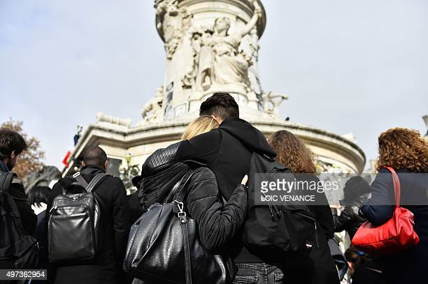 People gather after observing a minute of silence to pay tribute to victims of the attacks claimed by Islamic State on November 16 2015 at the Place...