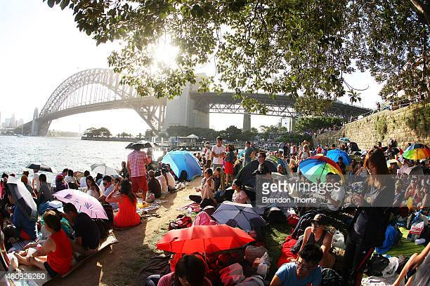People gather along Sydney Harbour to welcome in the New Year on New Year's Eve on Sydney Harbour on December 31 2014 in Sydney Australia