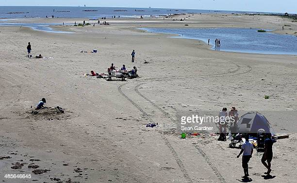 People gather along the beach in Grand Isle State Park days after a BP announcement that it is ending its active cleanup on the Louisiana coast from...
