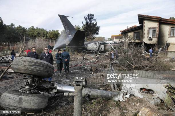 TOPSHOT People gather amid the debris of a Boeing 707 cargo plane that reportedly crashed into a residential complex near the Iranian capital Tehran...