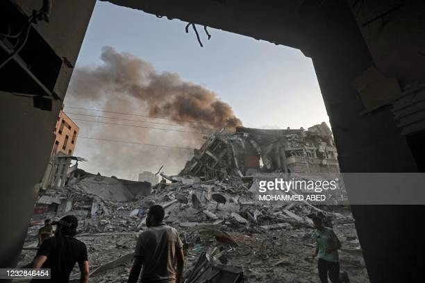People gather amidst the rubble in front of Al-Sharouk tower that collapses after being hit by an Israeli air strike, in Gaza City, on May 12, 2021....