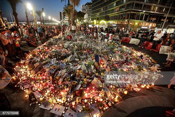 People gather and lay tributes on the Promenade des Anglais on July 17 2016 in Nice FranceA FrenchTunisian attacker killed 84 people as he drove a...