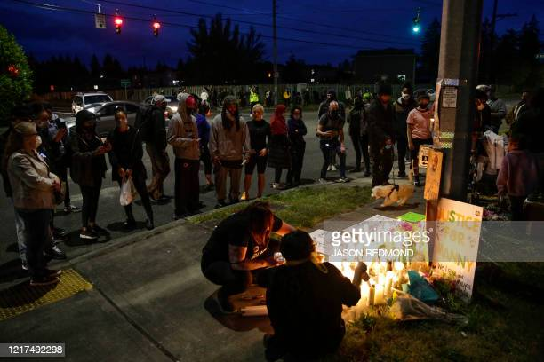 People gather and light candles at a makeshift memorial at the intersection where Manuel Ellis a 33yearold black man died in Tacoma Police custody on...