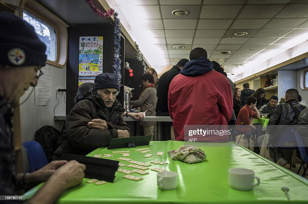 MOUTTET - People gather and play games aboard a barge of charity association 'Peniche Accueil' which welcomes every day in the afternoon homeless and people with financial difficulties , on December 27, 2012 in Lyon.