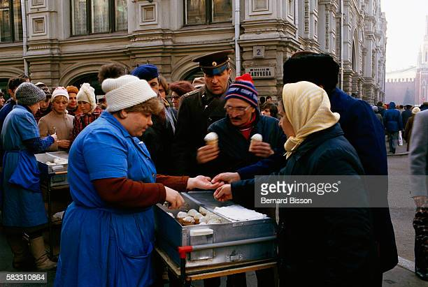 People gather and queue in front of two street vendors selling ice cream on a Moscow square during the Gorbachev era.