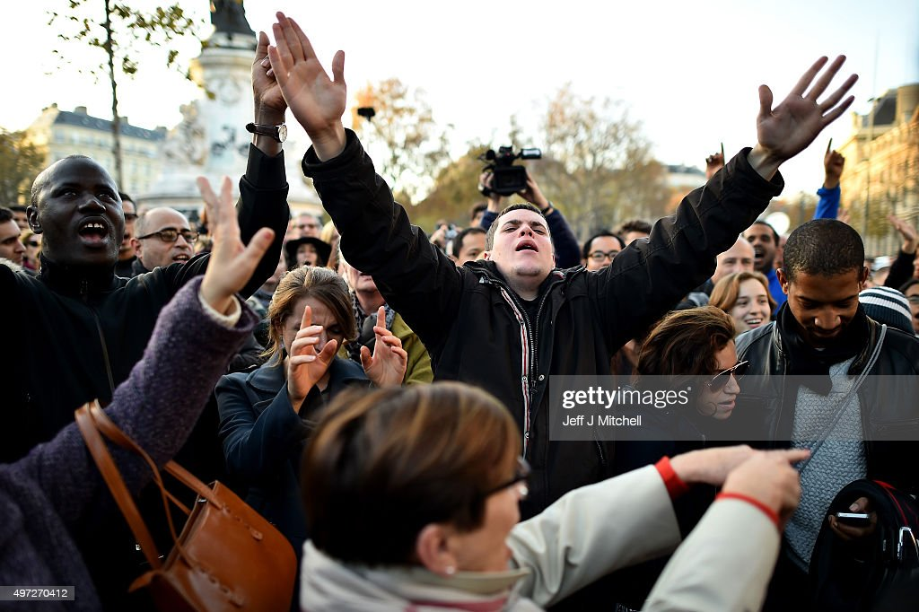 People gather and sing songs at Place de la Republique on November 15, 2015 in Paris, France. As France observes three days of national mourning members of the public continue to pay tribute to the victims of Friday's deadly attacks. A special service for the families of the victims and survivors is to be held at Paris's Notre Dame Cathedral.