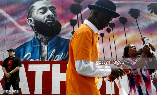 People gather and take photos in front of a mural to slain rapper Nipsey Hussle as they await the funeral procession for Hussle on April 11 2019 in...