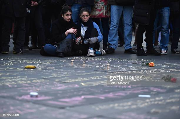 People gather and view messages written on the ground at Place de la Republique as France observes three days of national mourning for the victims of...