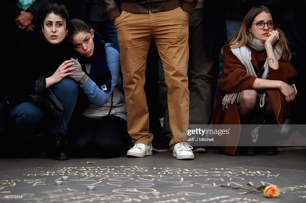 People gather and view messages written on the ground at Place de la Republique on November 15, 2015 in Paris, France. As France observes three days of national mourning members of the public continue to pay tribute to the victims of Friday's deadly attacks. A special service for the families of the victims and survivors is to be held at Paris's Notre Dame Cathedral.