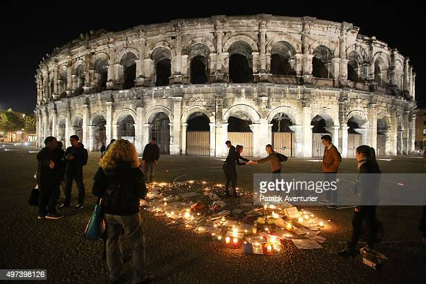 People gather and view messages written on the ground at the Nimes Roman arena in memory of the victims of the Paris terror attacks last Friday, on...