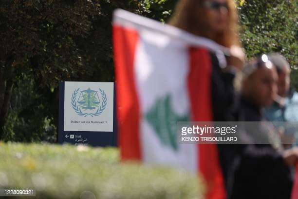 People gather and wave Lebanon national flags in front of the UN-backed Special Tribunal for Lebanon at Leidschendam on August 18 before the expected...
