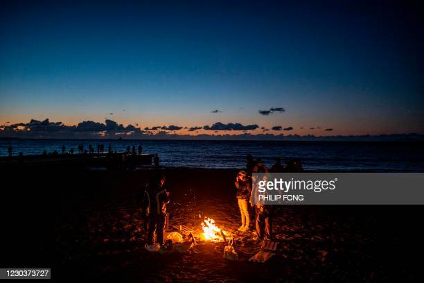 People gather around a bonfire at Southern Beach of Chigasaki to watch the sunrise on New Year's Day in Kanagawa Prefecture, southwest of Tokyo on...