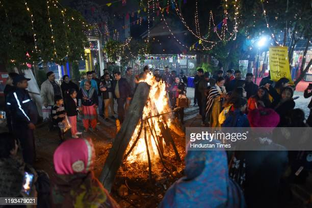 People gather around a bonfire during Lohri celebrations at Delhi Haat INA on January 13 2020 in New Delhi India
