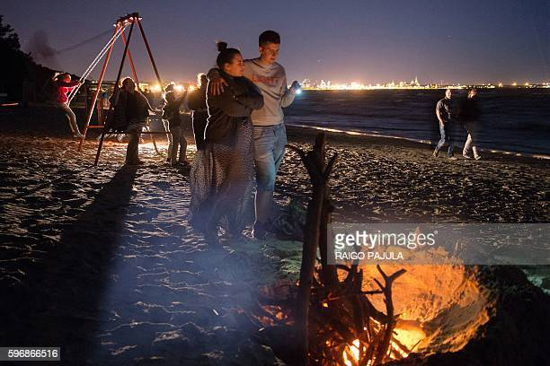 People gather around a bonfire during the Night of Ancient Bonfires a centuriesold maritime tradition also focused now on environmental awareness on...
