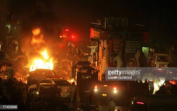 People gather around a burning car in front of a vehicle carrying of former Pakistani prime minister Benazir Bhutto after suicide attack in Karachi...
