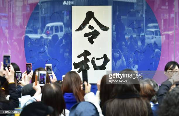 People gather around a calligraphic work showing Japan's new era name Reiwa in Tokyo's Ginza shopping district on April 1 2019 The new era will begin...