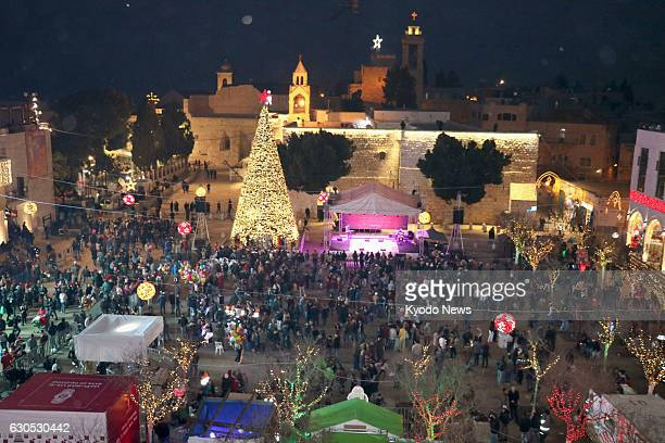 People gather around a Christmas tree in Manger Square in front of the Church of the Nativity in the West Bank town of Bethlehem on Dec 24 2016 Many...