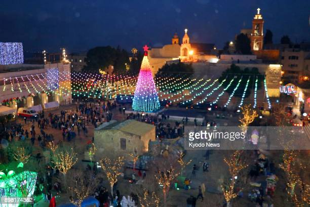People gather around a Christmas tree in Manger Square in front of the Church of the Nativity in the West Bank town of Bethlehem on Dec 24 amid...