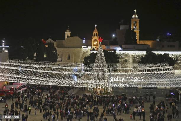 People gather around a Christmas tree near the Church of the Nativity in Bethlehem on Dec. 24, 2019.