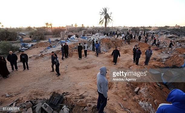 People gather around a damaged area after US warplanes carried out air strikes against Daesh training camp in western Libya on February 19 2016