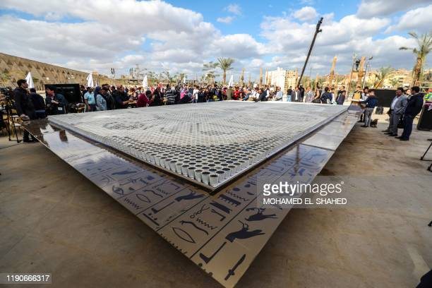 People gather around a depiction of the ancient Egyptian Pharaoh Tutankhamun's death mask made of 7260 cups of coffee, in front of the newly-built...