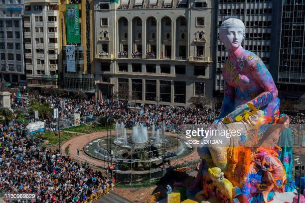 People gather around a 'falla' to watch the traditional 'Mascleta' during the Fallas festival in Valencia on March 16 2019