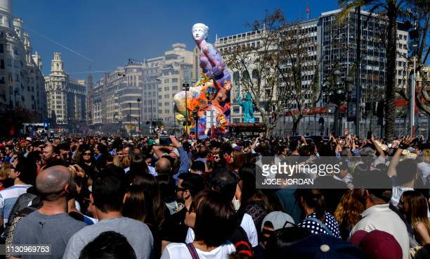 People gather around a 'falla' to watch the traditional 'Mascleta' during the Fallas festival in Valencia on March 16, 2019.