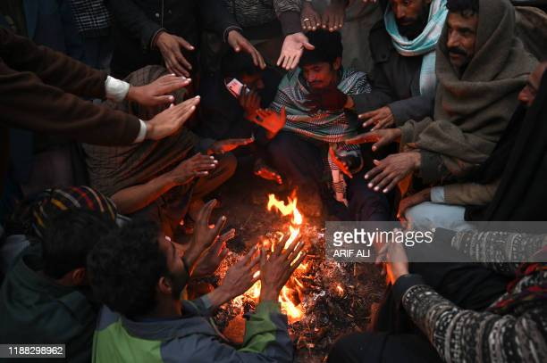 People gather around a fire during cold day in Lahore on December 13 2019