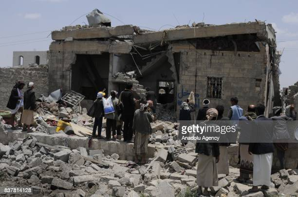 People gather around a heavily damaged building after Saudiled coalition's air strikes over Arhab District of Sanaa Yemen on August 23 2017 At least...