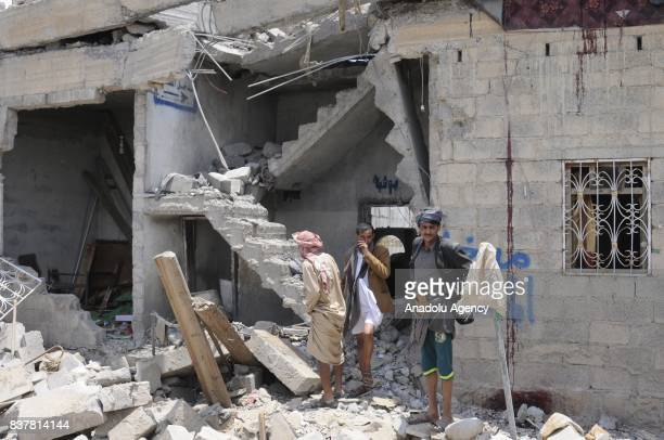 People gather around a heavily damaged building after Saudi-led coalition's air strikes over Arhab District of Sanaa, Yemen on August 23, 2017. At...