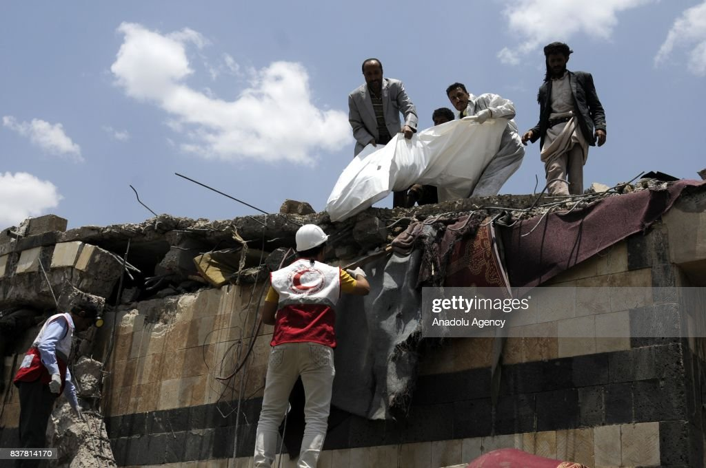 People gather around a heavily damaged building after Saudi-led coalition's air strikes over Arhab District of Sanaa, Yemen on August 23, 2017. At least 20 Shia Houthi militia group members were killed due to the attack.