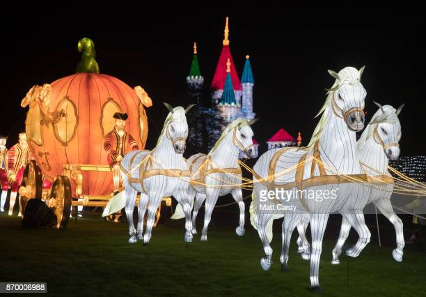 People gather around a illuminated horse drawn pumpkin carriage as they enjoy the spectacle at the opening night of annual Festival of Light at the...