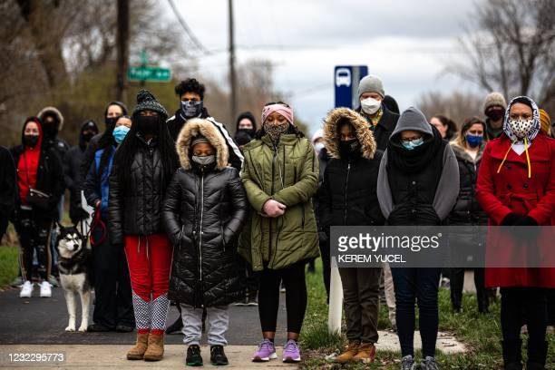 People gather around a makeshift memorial for Daunte Wright at a sculpture of a raised fist in Brooklyn Center, Minnesota on April 13, 2021. -...