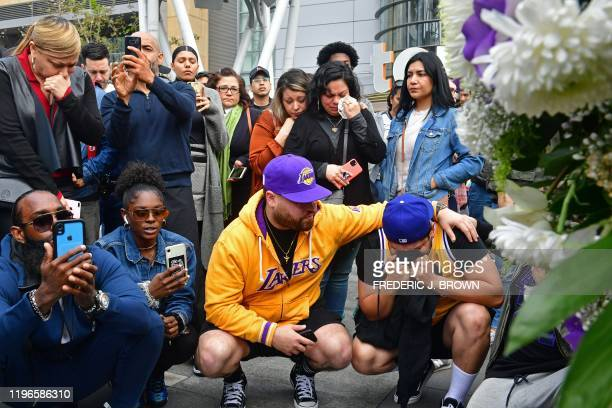 People gather around a makeshift memorial for former NBA and Los Angeles Lakers player Kobe Bryant after learning of his death at LA Live plaza in...