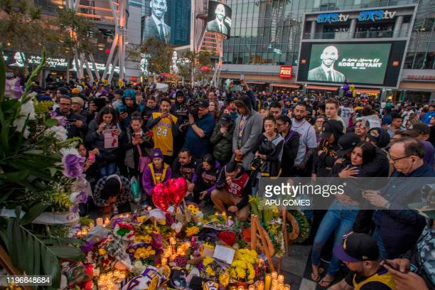 TOPSHOT People gather around a makeshift memorial for former NBA and Los Angeles Lakers player Kobe Bryant after learning of his death at LA Live...