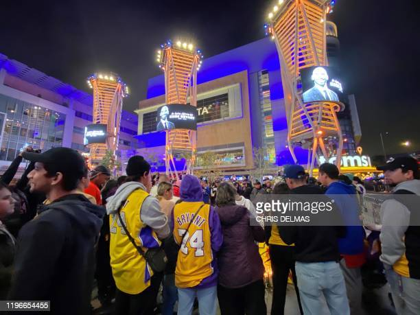 People gather around a makeshift memorial for late basketball legend Kobe Bryant at the Staples center in Los Angeles on January 26 a few hours after...