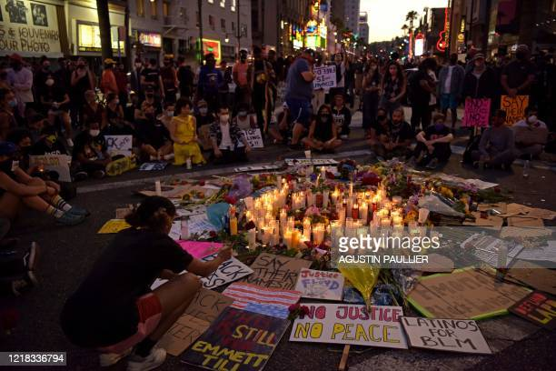 TOPSHOT People gather around a makeshift memorial in honor of the victims of police brutality during a demonstration against racism in Hollywood...