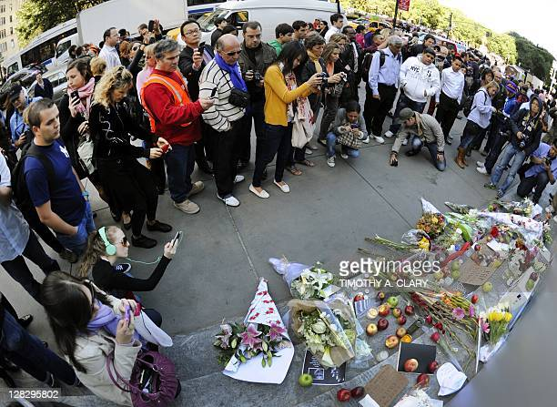 People gather around a makeshift memorial outside the Apple Flagship store on 5th Avenue in New York October 6 2011 the morning after the death of...