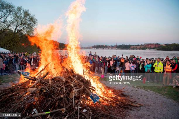 People gather around a May bonfire as they celebrate Walpurgis Night in Stockholm late April 30 2019 Walpurgis Night in Sweden is a traditional...